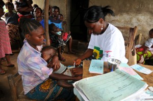Children receive vaccinations in Kingsville, Liberia. To help reach remote villages that are many hours walk from Kingsville clinic in Liberia, Save the Children has provided motorbikes for vaccinators to take the vaccines to the villages.  Although child mortality rates have dropped in Liberia, maternal mortality rates have risen. One in twelve women dies during child birth. Save the Children is training midwives in safe delivery practices and encouraging pregnant women to come to the clinic during pregnancy for regular checks and to bring their children for essential vaccinations..One in nine children die in Liberia from easily preventable diseases and the country has one of the worst newborn death rates in Africa. But the country is making progress thanks to simple steps such as widespread vaccination programmes, mosquito net distributions and a commitment to making healthcare free for even the poorest families. 25,000 more children now survive to their fifth birthdays compared to a few years ago. Save the Children is supporting clinic's such as Kingsville to help reduce maternal and child mortality rates.
